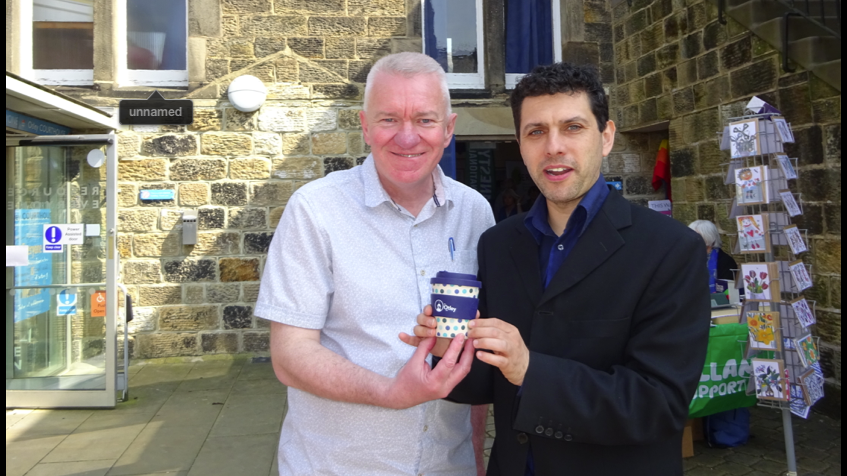 Otley Green Fair 2019. Alex Sobel MP and Ray Georgsson Leader of the Otley Council holding reusable coffee mugs at the Green Fair 2018.